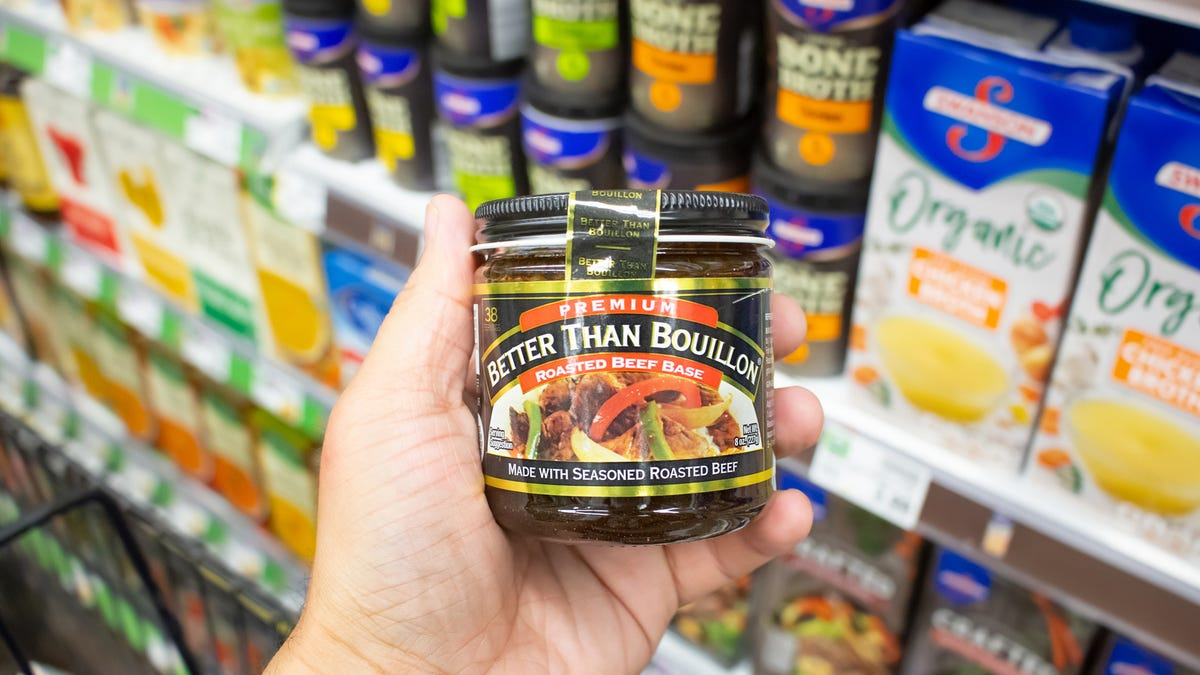 A shopper holding up a container of Better than Bouillon in a grocery store.