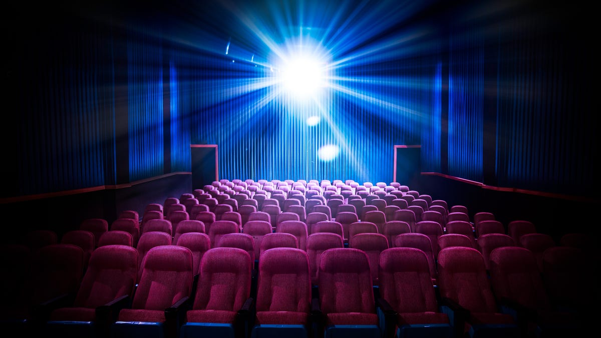 A blue light shines across red seats in a movie theater.