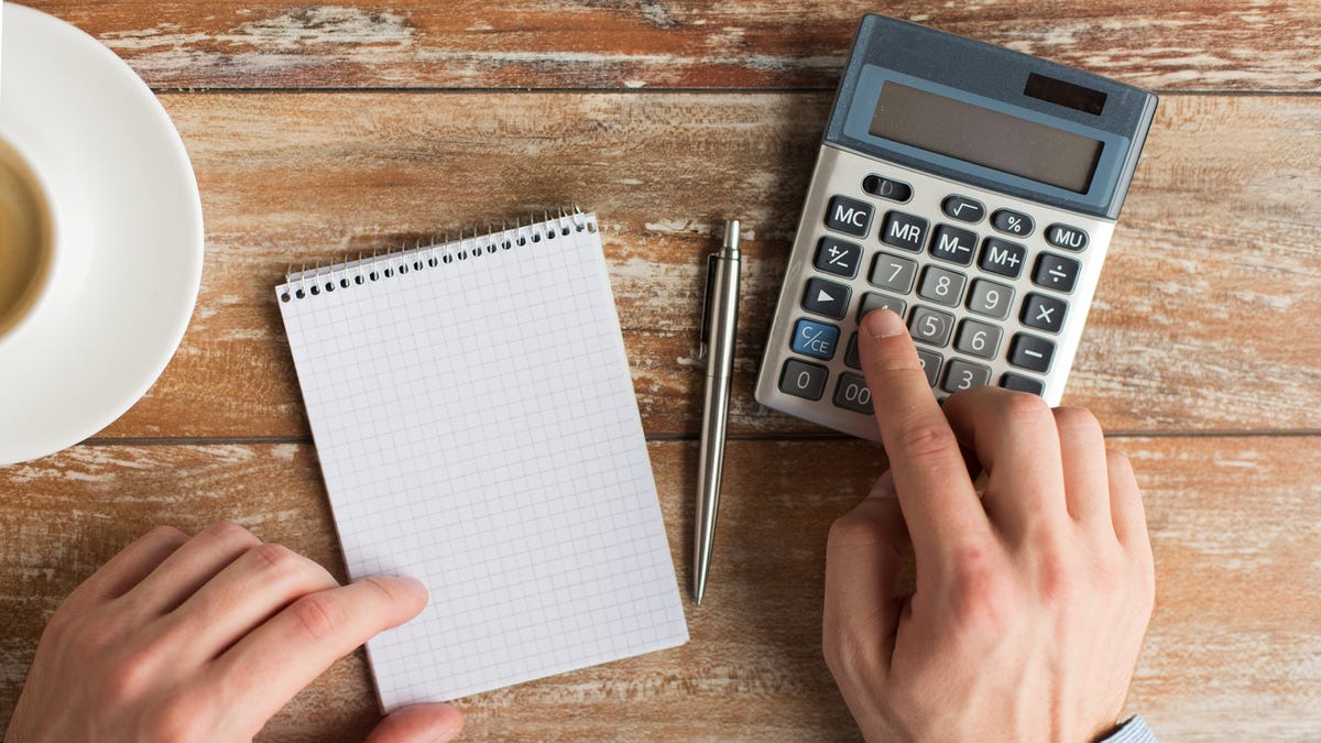Close-up of male hands with calculator, pen, and notebook on table a wooden table.