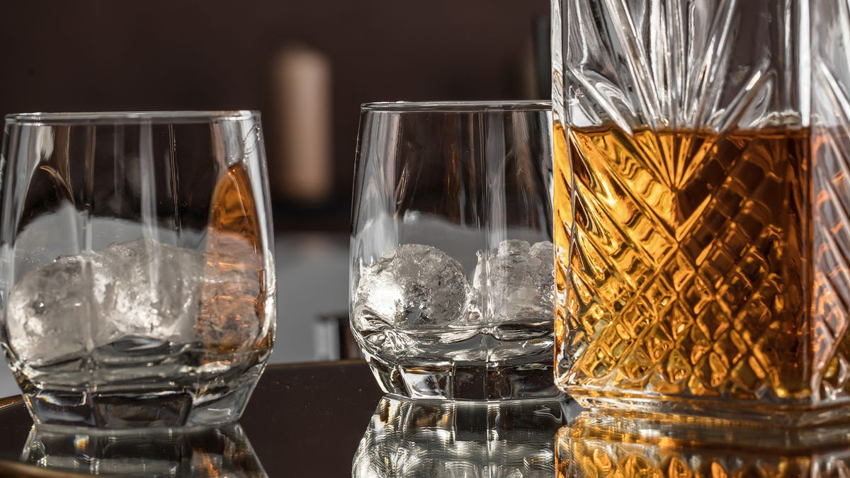 Two glasses sit next to a decanted bottle of liquor.