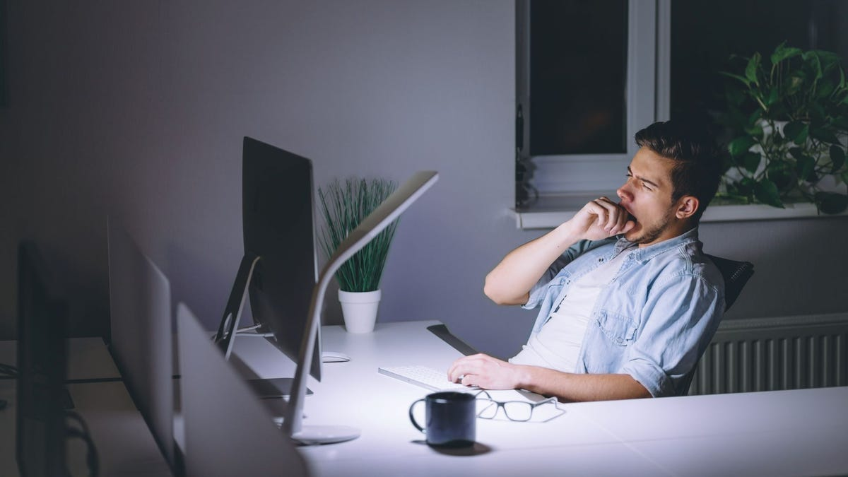 A man yawning while staring at a computer in his home office at night.