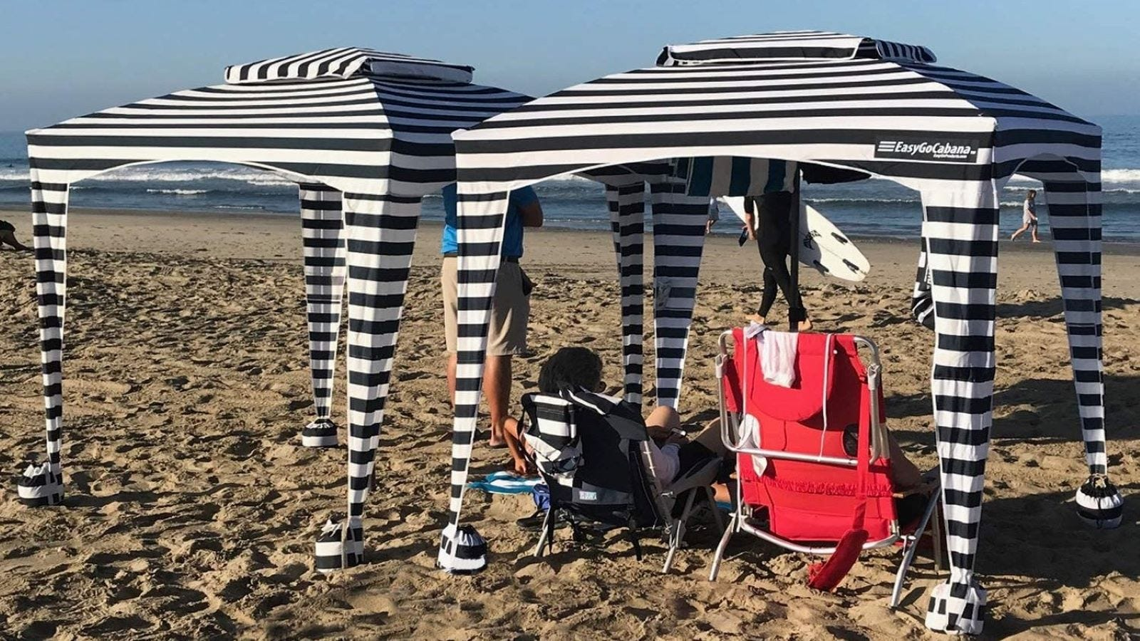 Two people at the beach under two blue-and-white striped EasyGo Cabanas.