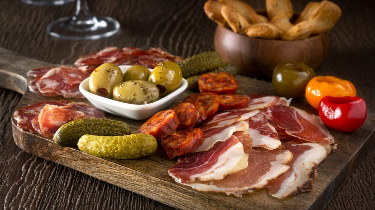 A collection of charcuterie meats, pickles, and olives sit on a wooden cutting board.