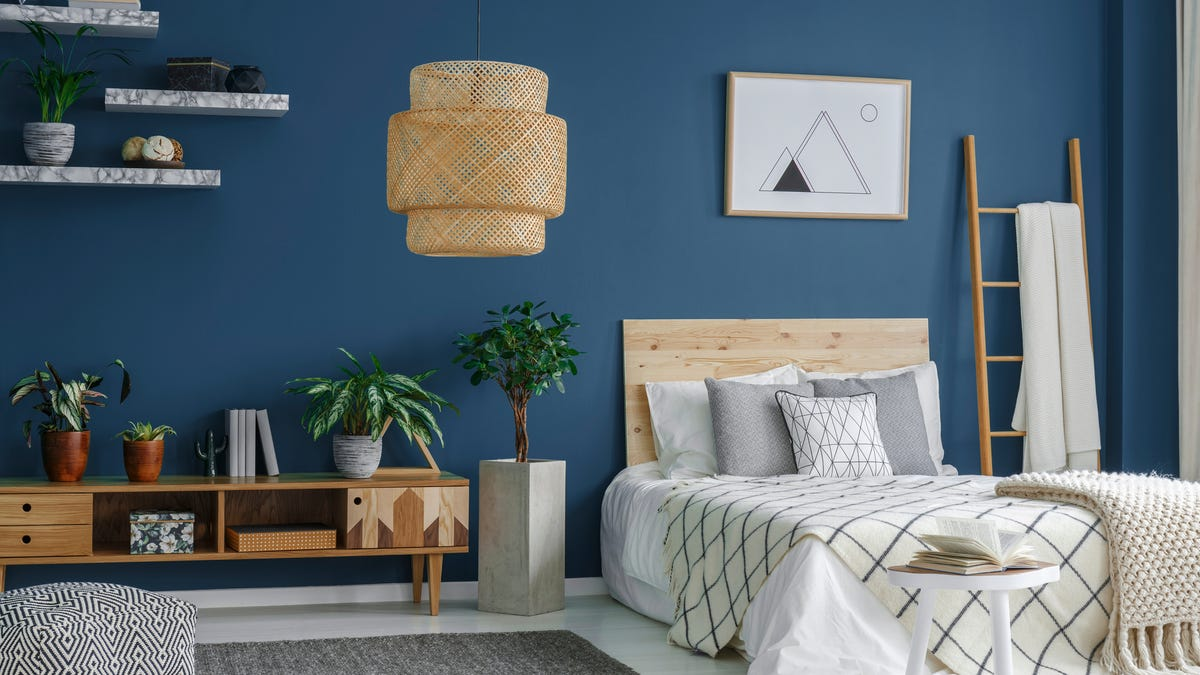 A wall is painted a deep blue in a bedroom featuring white bedroom and rattan accents.