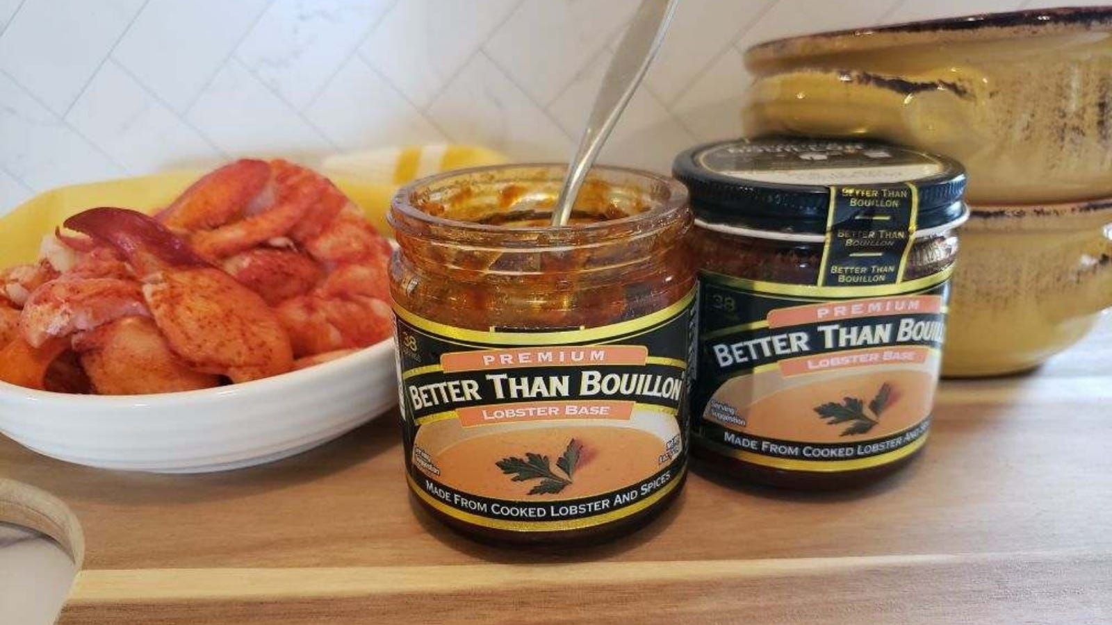 'Two jars of lobster base by Better than Bouillon with two crocks and a small bowl of lobster in teh background.