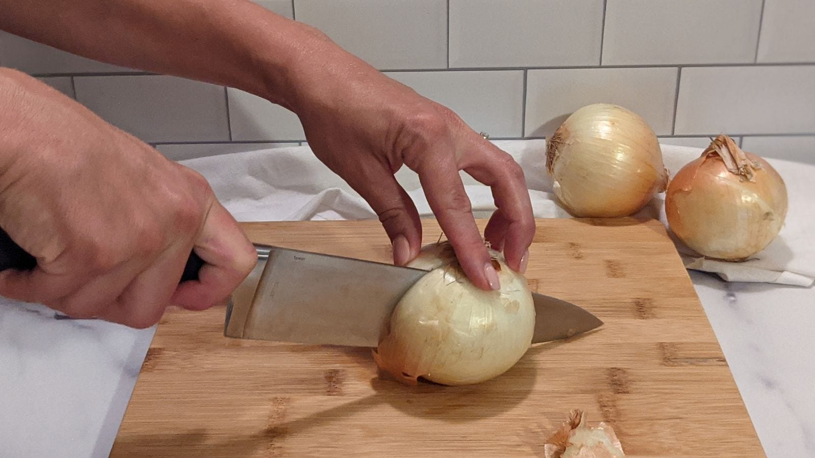 Slicing an onion in half before peeling it.