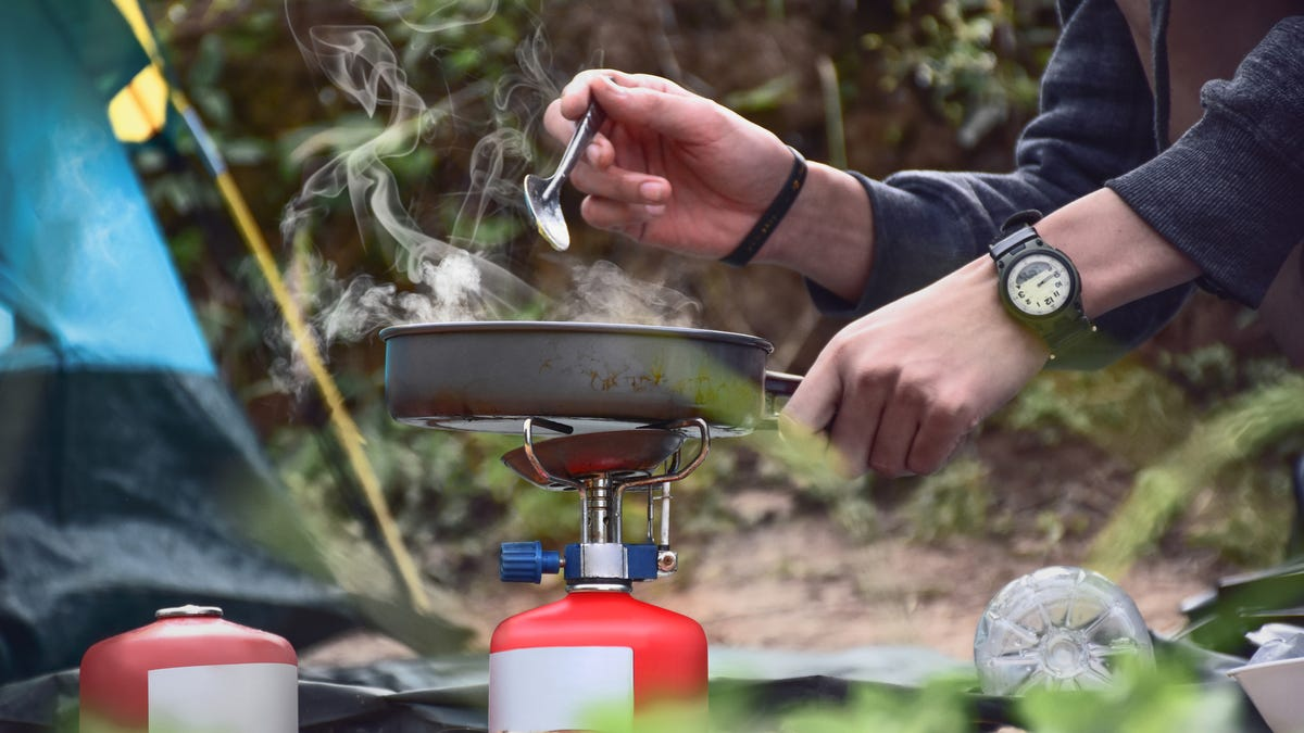 Somone cooking at their campsite using their hiking cookware, stove and a fuel tank.