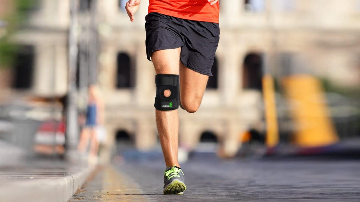 A man running in the street with a black knee brace on his left knee.