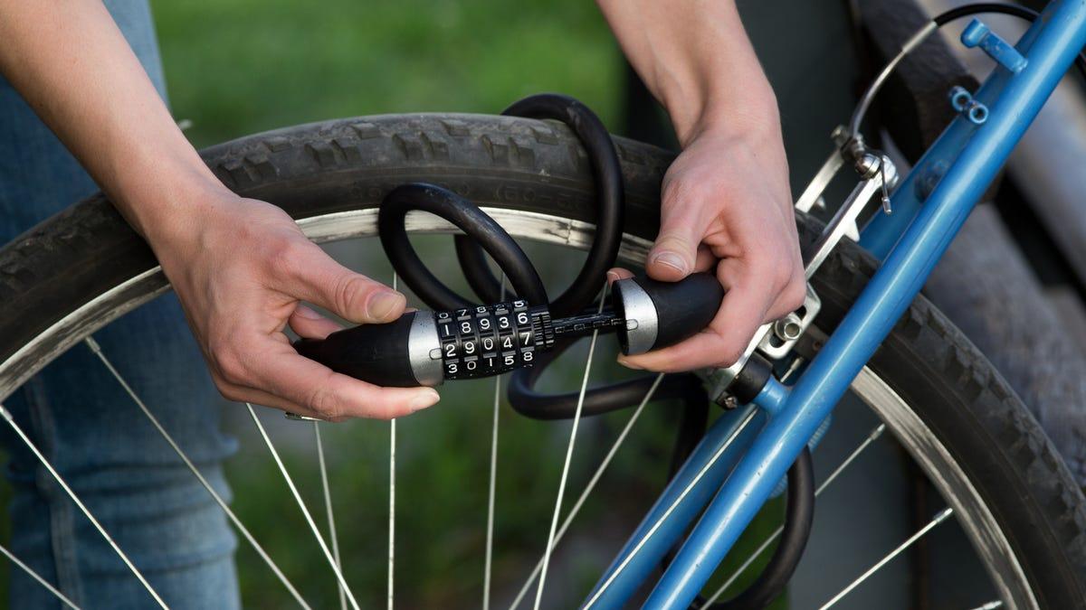 A person attaches a bike lock through the tire of their bike.