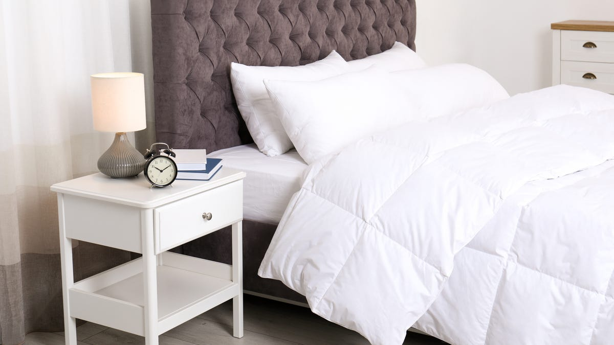 A white nightstand with a clock, books, and lamp sits next to a bed with white bedding.