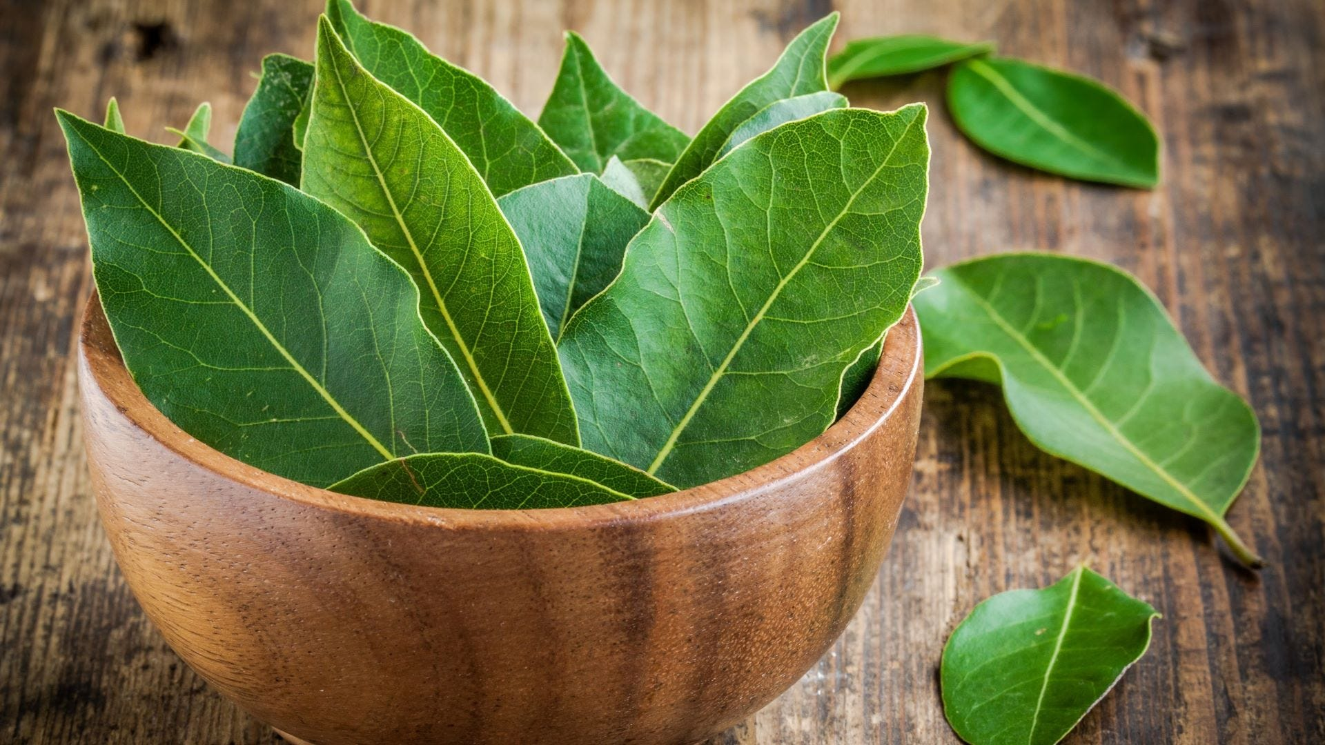 A wooden bowl full of bay leaves.
