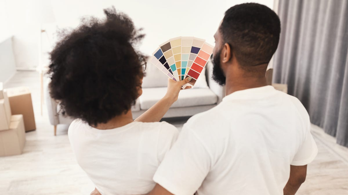 A couple looks at paint swatches held up against a white wall.