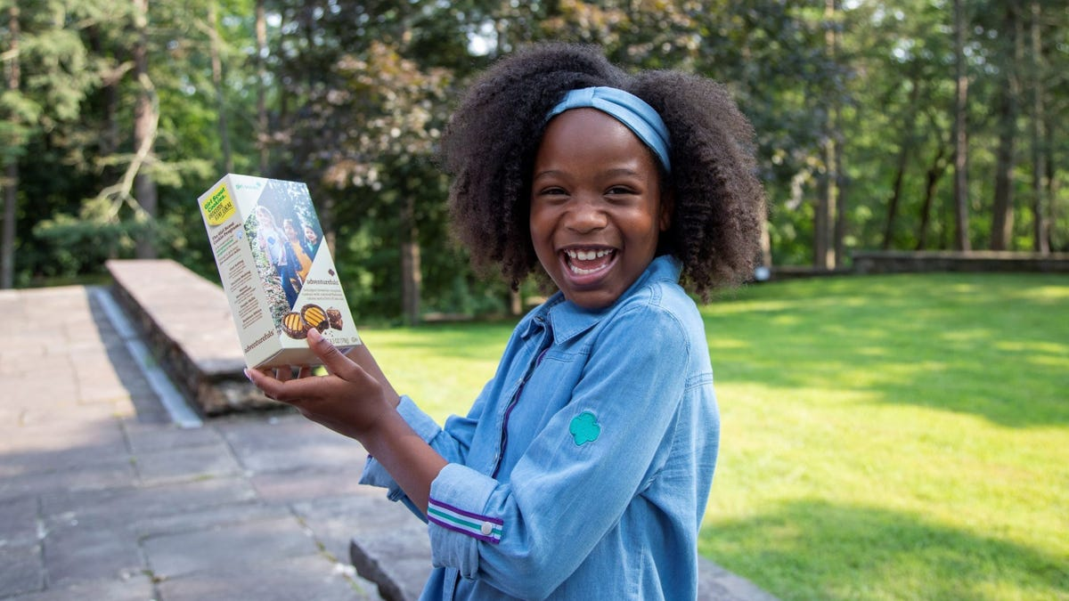 A Girl Scout holds up a box of the organization's new cookie.