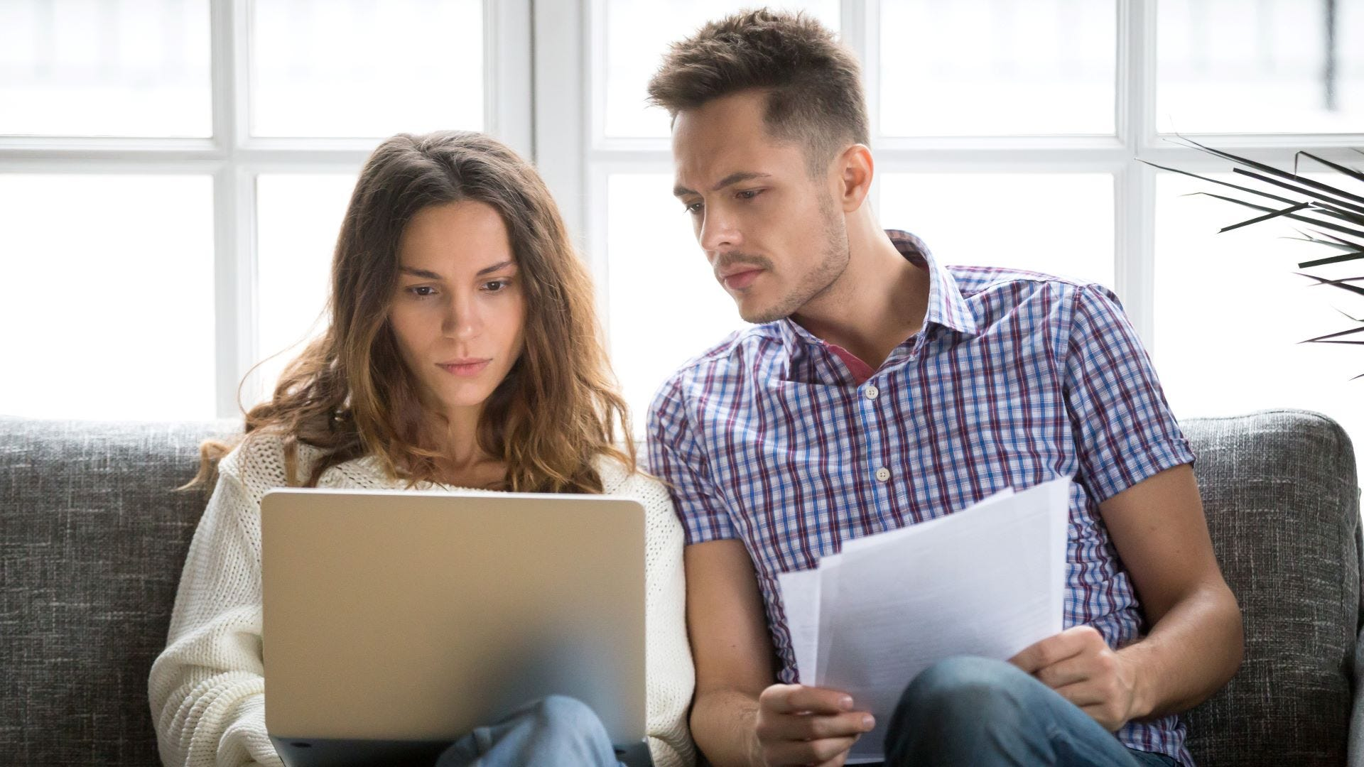 A couple paying bills online on a laptop.