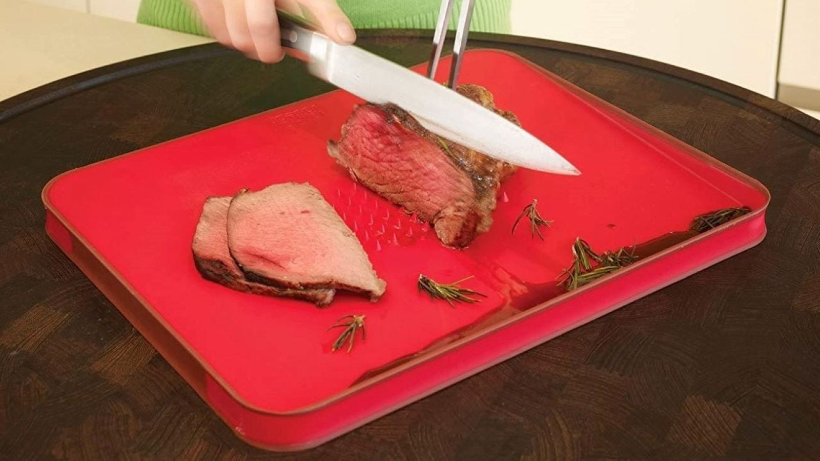 Someone slicing roast beef on the Joseph Joseph Meat Cutting Board.