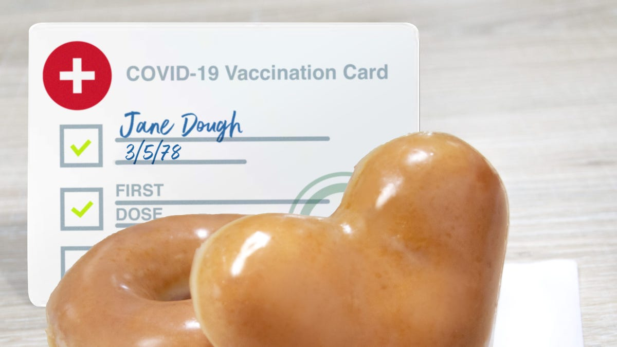 A regular doughnut and a heart shaped doughnut sit in front of an illustrated COVID-19 vaccine card.