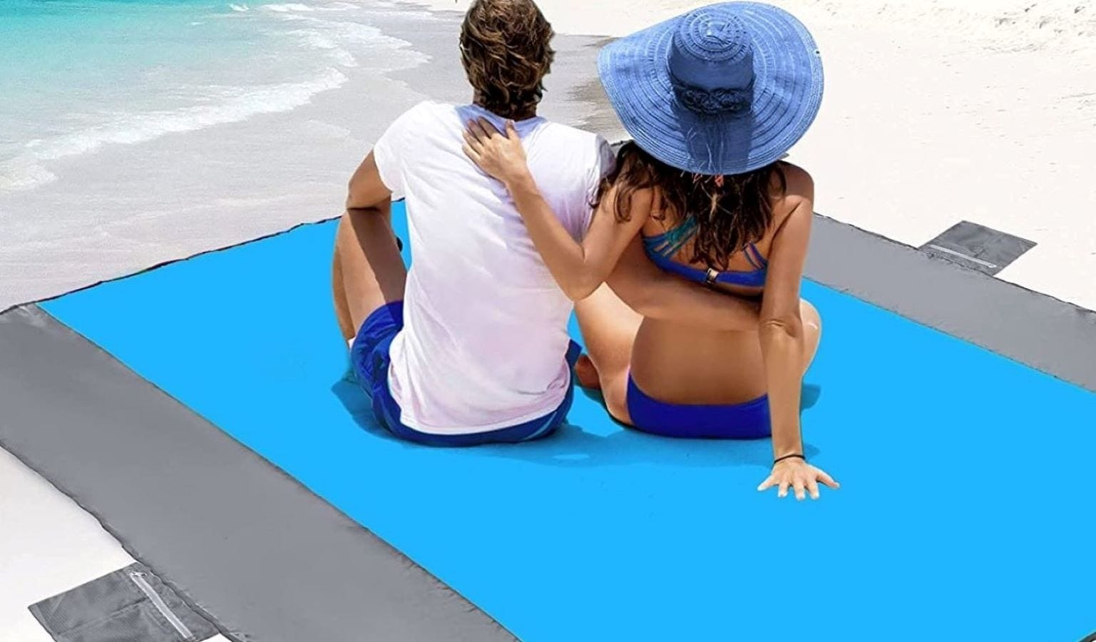 A man and woman sitting on the POPCHOSE Sandfree Beach Blanket at the beach.