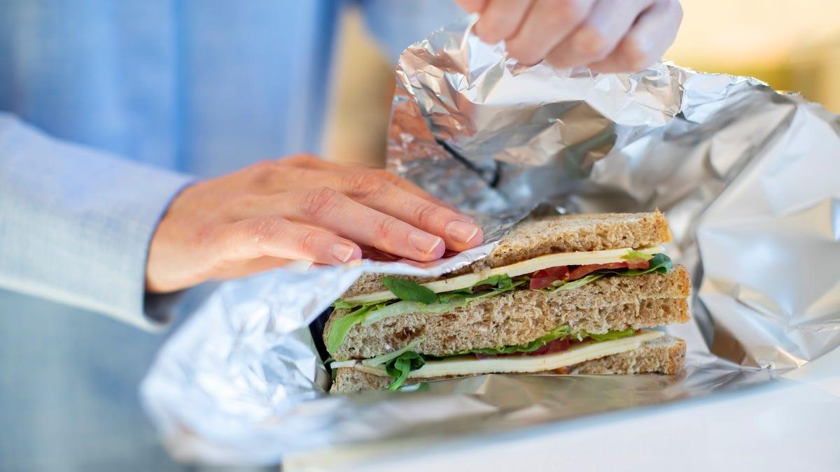 A person uses aluminum foil to wrap sandwich.