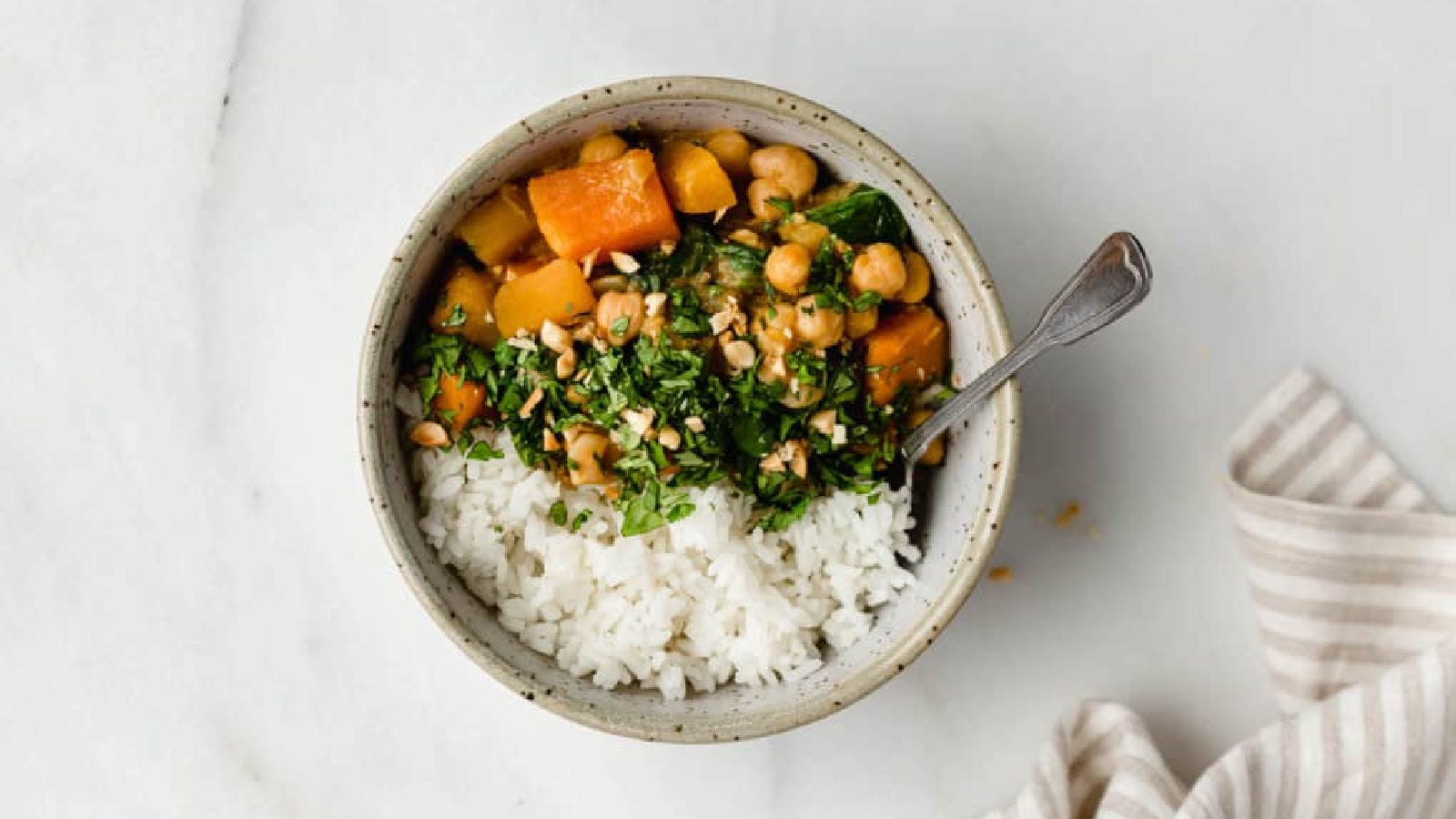 A bowl of thai-style pumpkin and chickpea curry topped over jasmine rice.