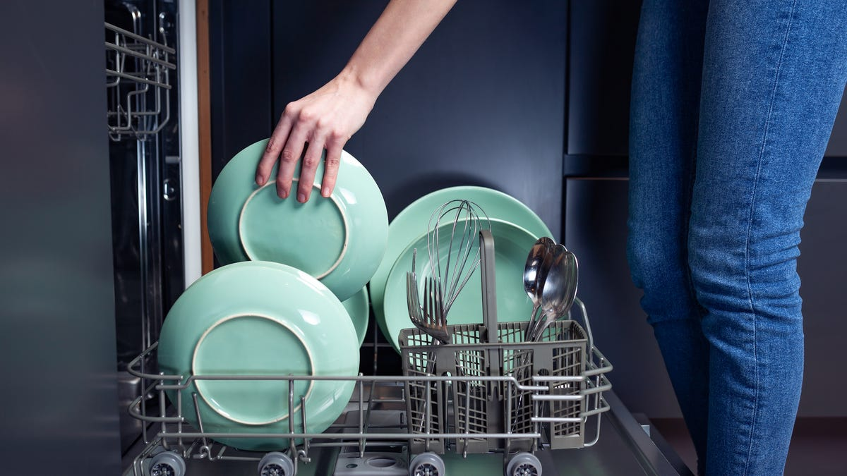 A person places dishes into a dishwasher.