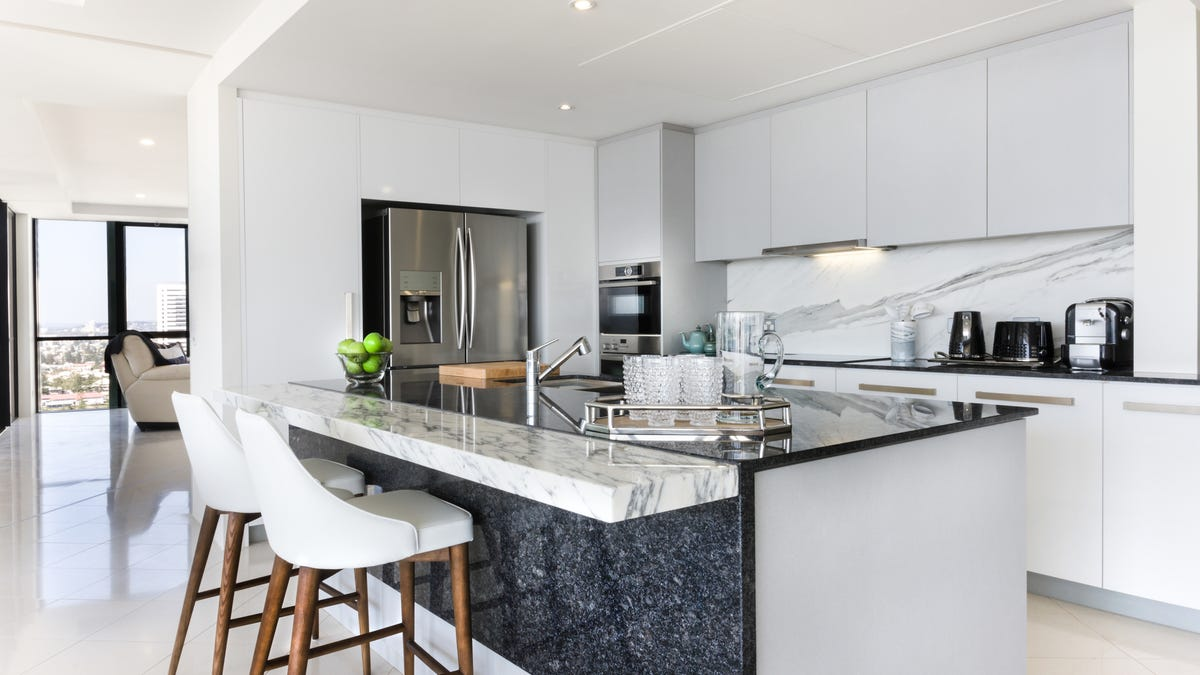 A modern kitchen features gray marble, white handleless cabinets, and sleek counters.