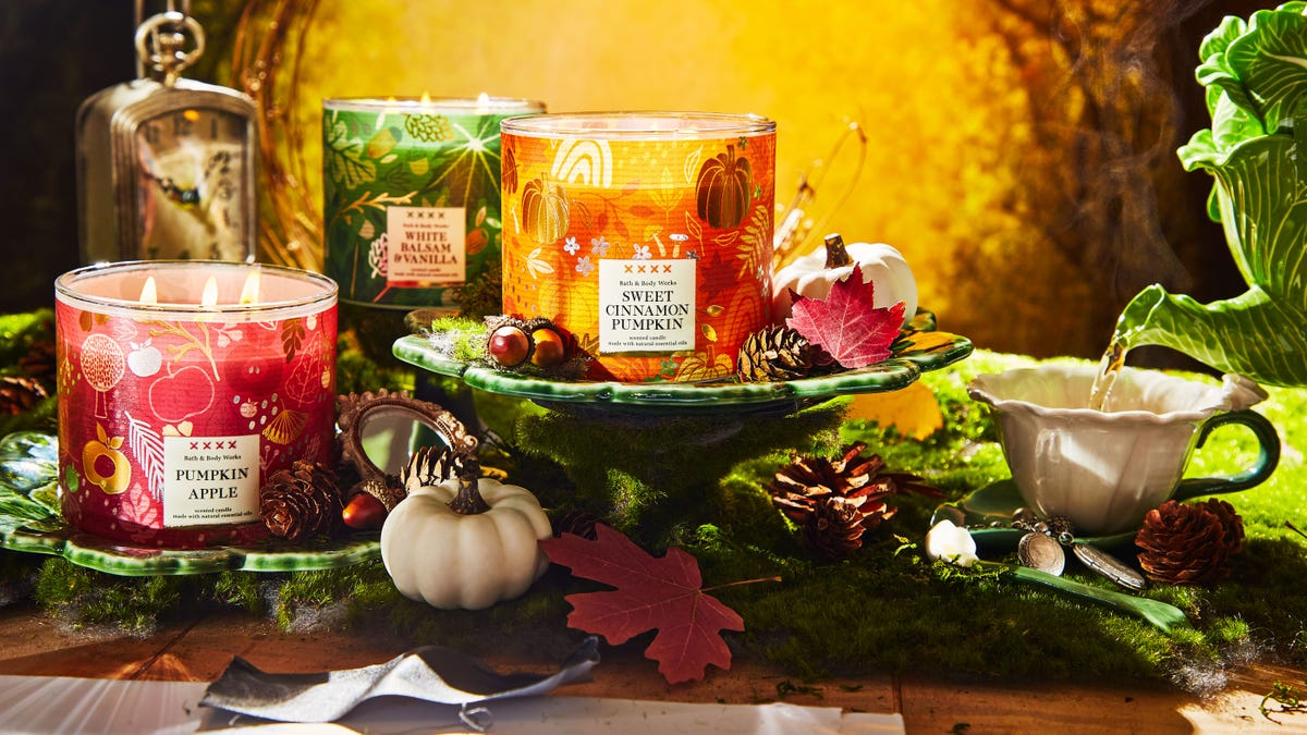A collection of three candles in red, gold, and green sit on top of moss-covered platforms surrounded by pumpkins.