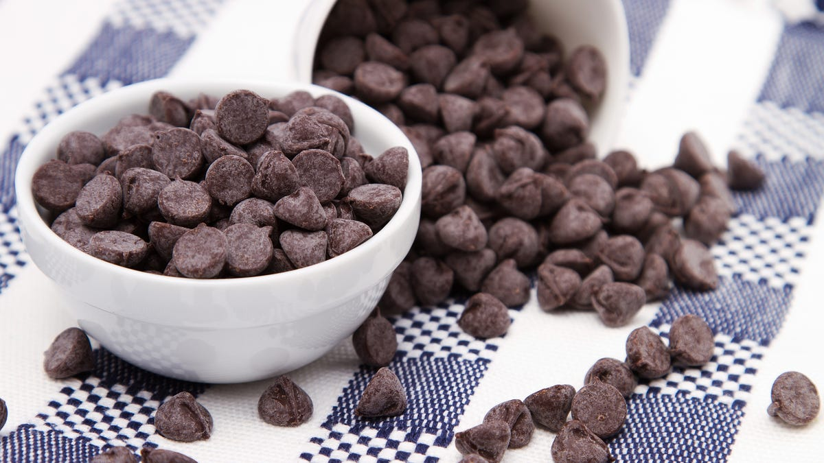 A bowl of chocolate chips sits on top of a checkered table cloth with other chips spilled around it.