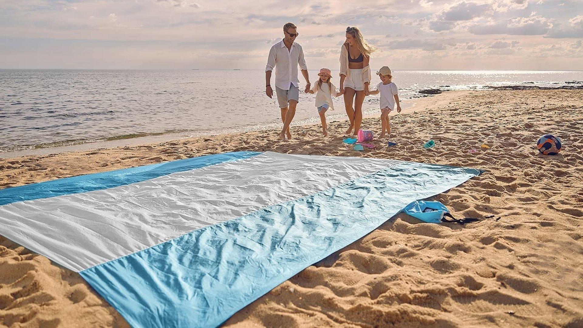 A family walks along the beach near a large beach blanket