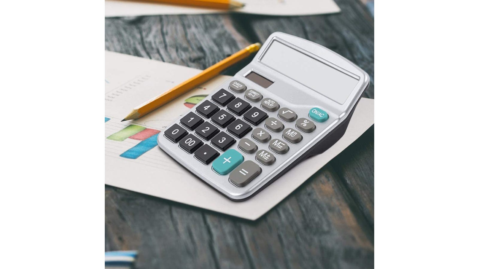 A basic calculator sitting on a desk next to papers.