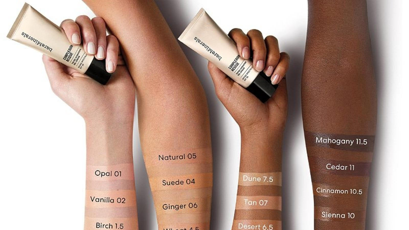hands in different skin tones holding bareMinerals tubes