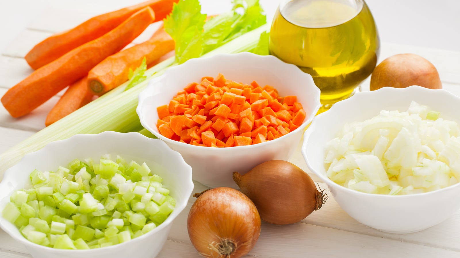 Three little bowls filled with aromatic ingredients including onion, celery and carrots with oil in the background.