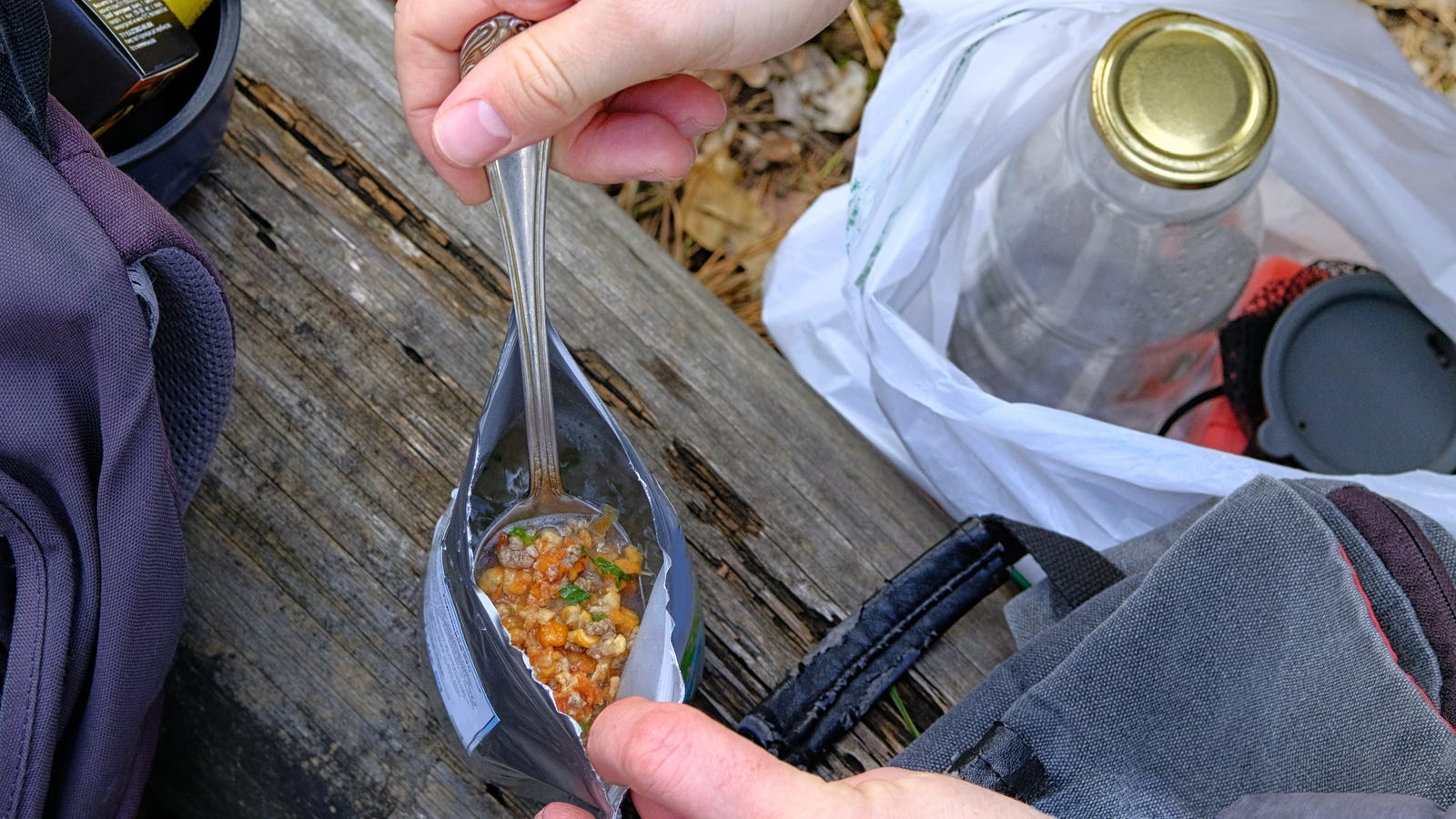 A hiker getting ready to enjoy a hot freeze dried meal while on a backpacking trip.