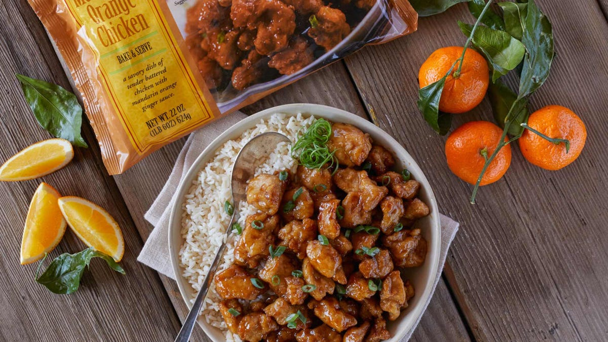 Orange chicken and rice in a bowl on a wooden table surrounded by oranges.