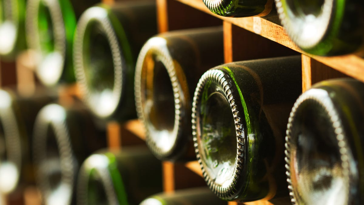 Glass wine bottles are stacked on their sides on a wooden rack.