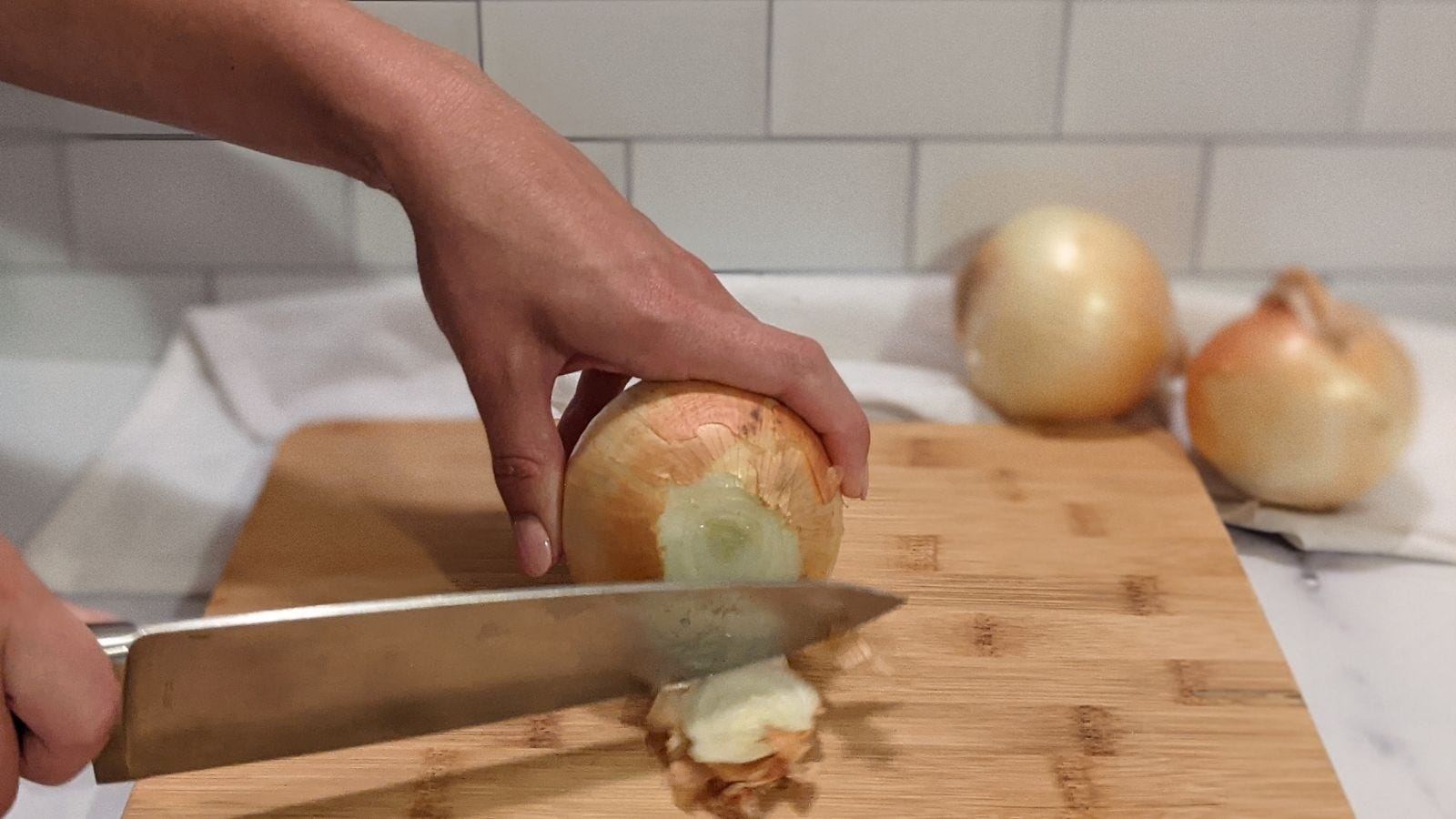 Slicing the stem of an onion off.