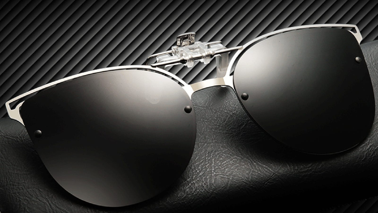 Clip-on sunglasses sit on a black textured surface.