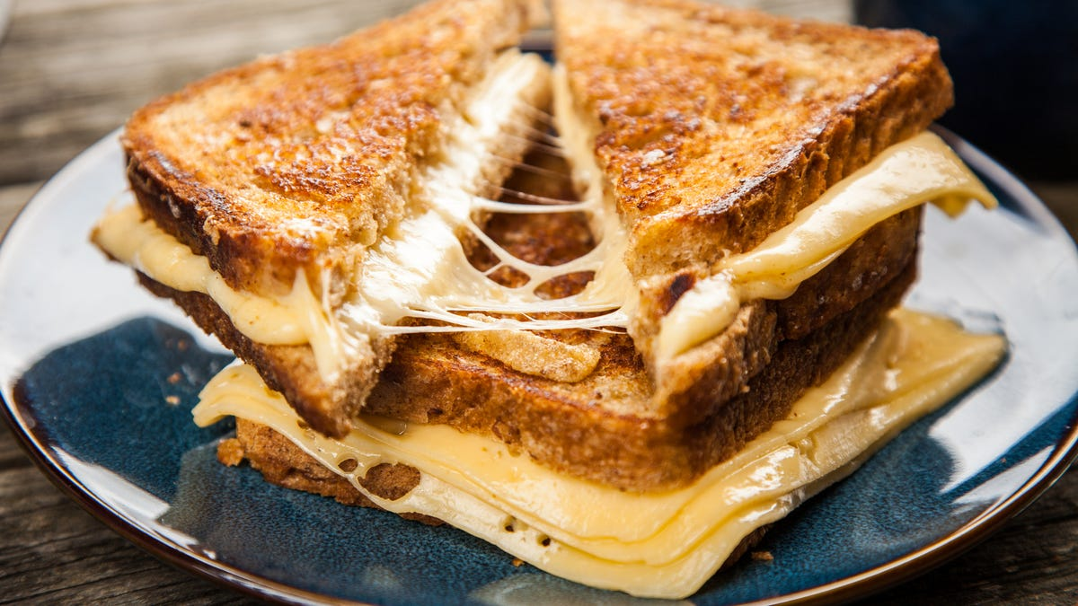 A grilled cheese is cut diagonally and pulled apart.