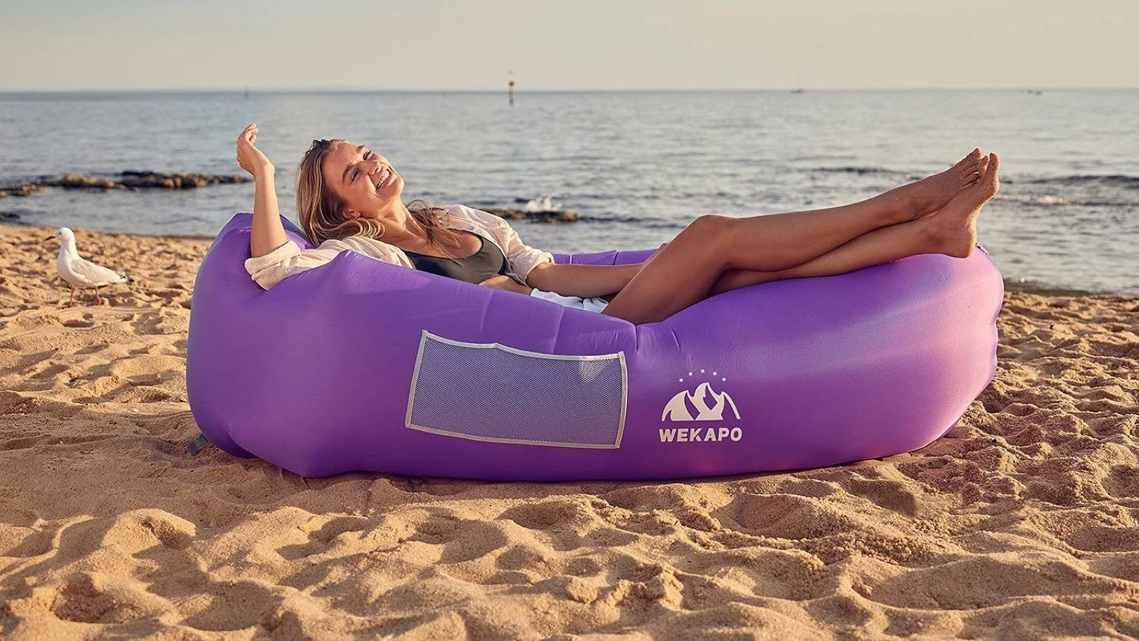 A woman at the beach in a purple Wekapo Lounger.