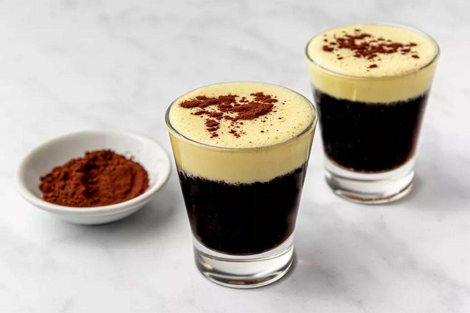 two small glasses with Vietnamese coffee in them, next to a small bowl with cocoa powder, on a marble counter.