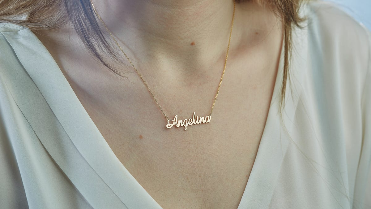 """A woman wears a gold necklace that says """"Angelina."""""""