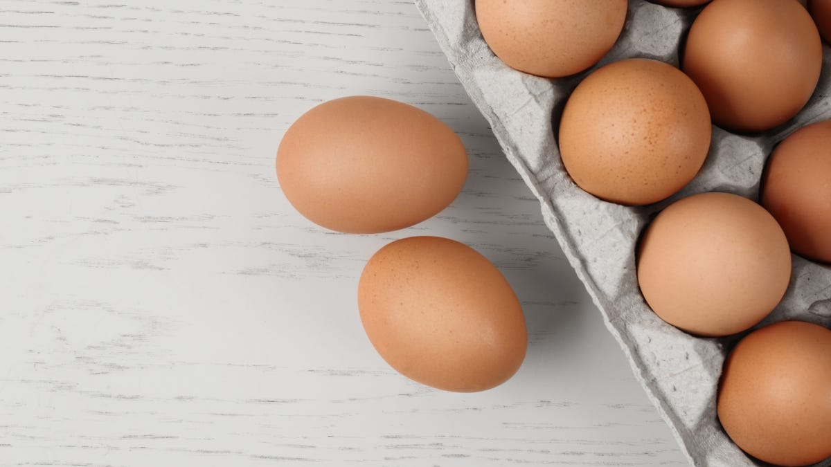 Two eggs sit beside a full carton.