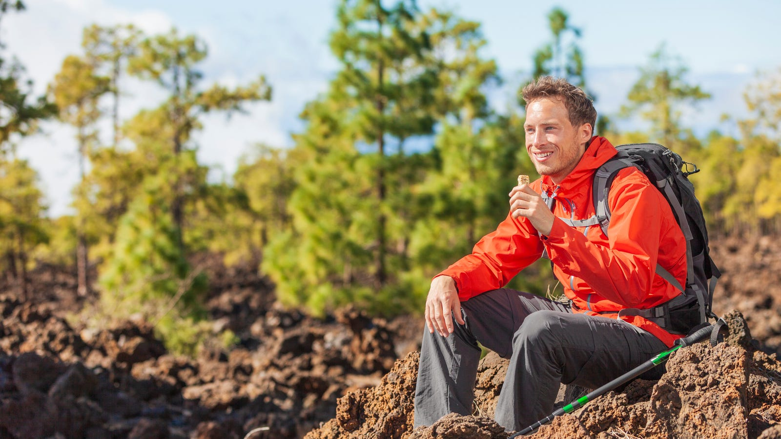 A hiker sitting down taking a break while enjoying a granola bar.