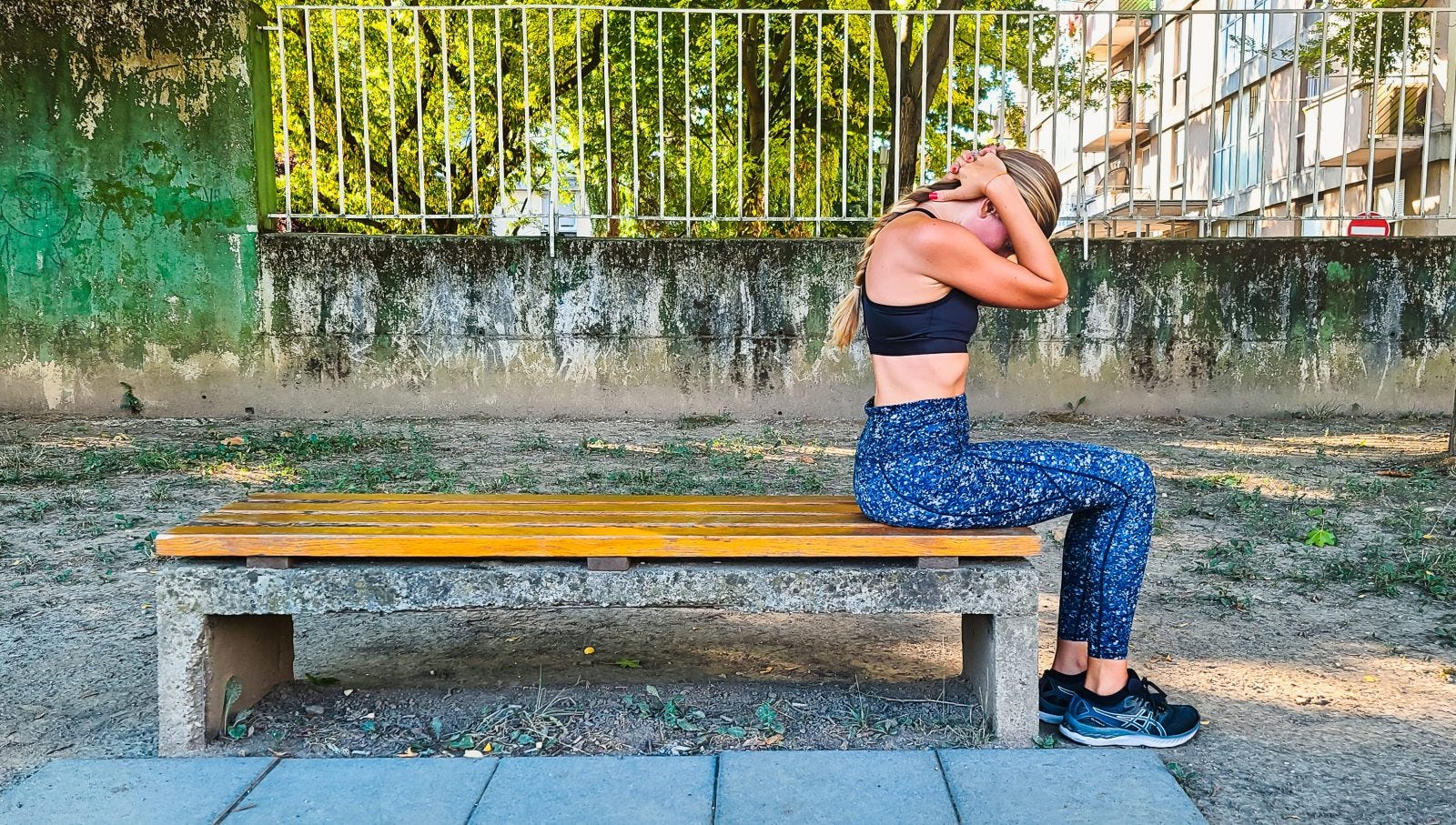 Woman doing a neck stretch on a bench in a park.