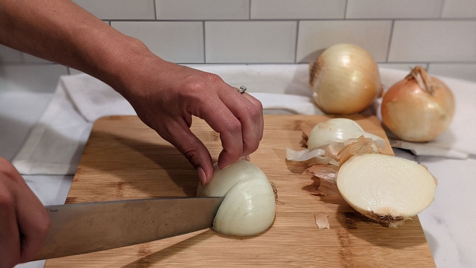 Slicing an onion multiple times vertically with a few onions and peels in the background.