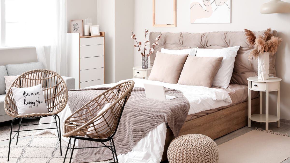 A bedroom features a stuffed headboard, neutral colors, and fluffy botanical accents.
