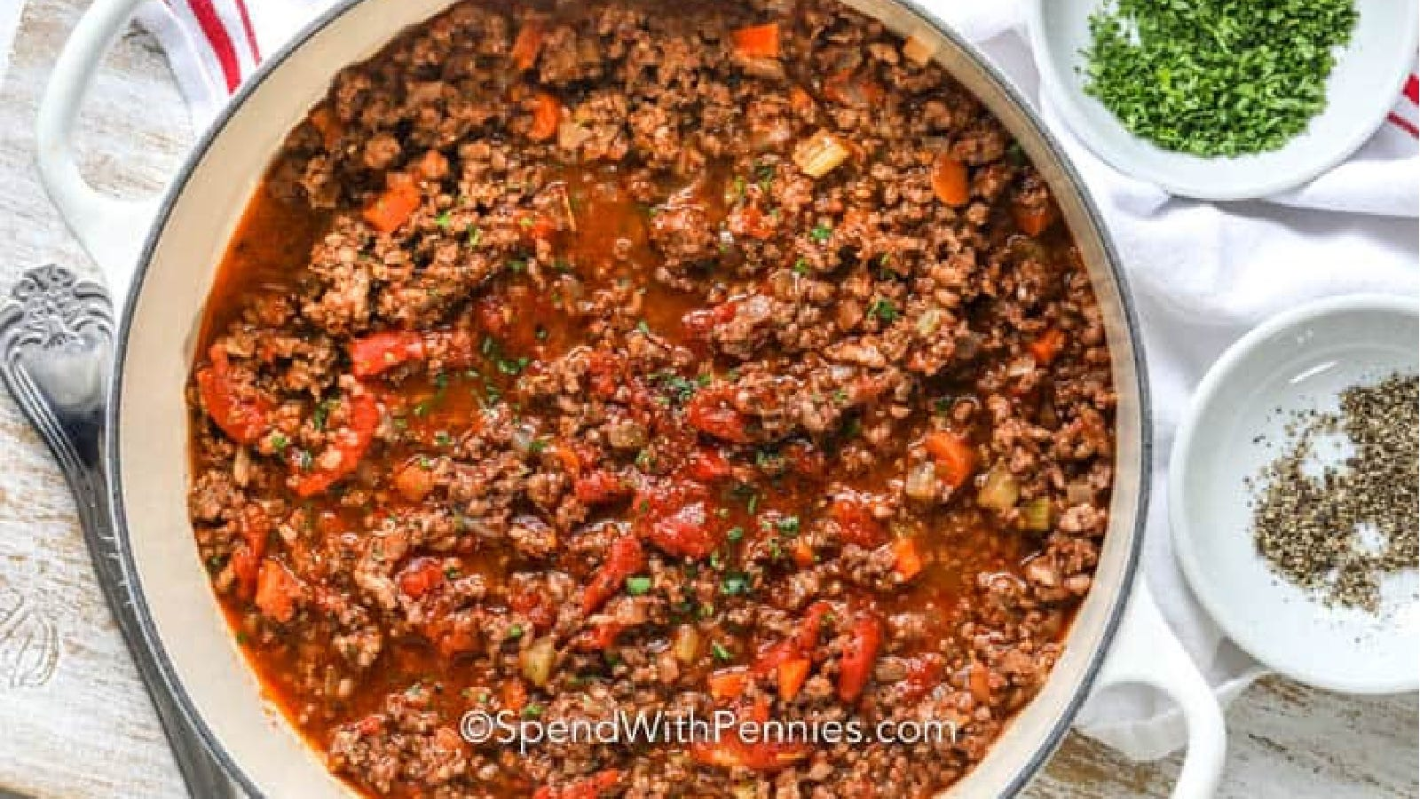 An enamed cast iron Dutch oven filled with a hearty bolognese sauce with pepper and herbs on the side.