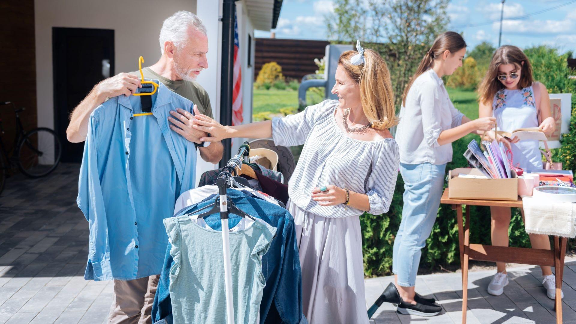 A man and woman looking at a shirt at a yard sale.