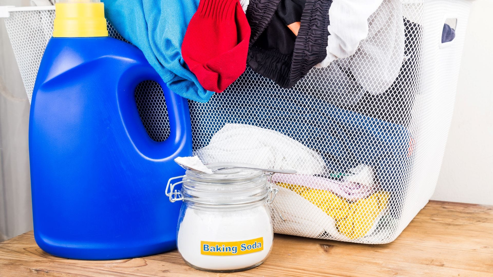 A jar of baking soda next to a bottle of laundry detergent and a basket full of dirty laundry.