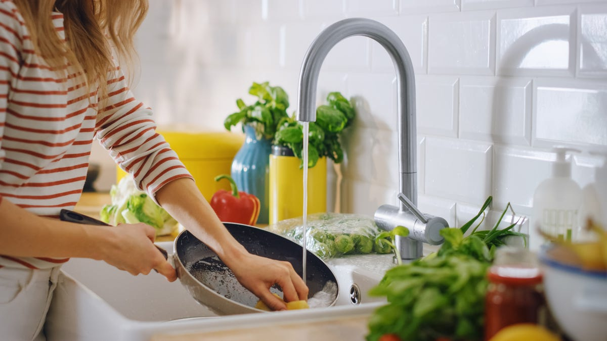 A woman uses a sponge to scrub a pan as water from a faucet flows into it.