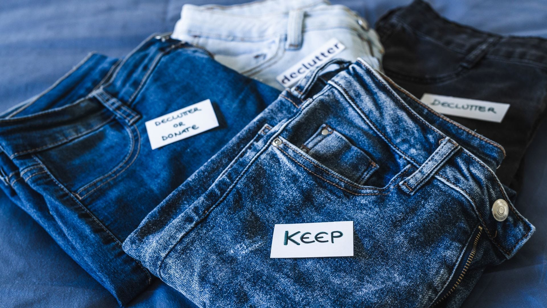 Four pairs of jeans labeled to be kept or donated
